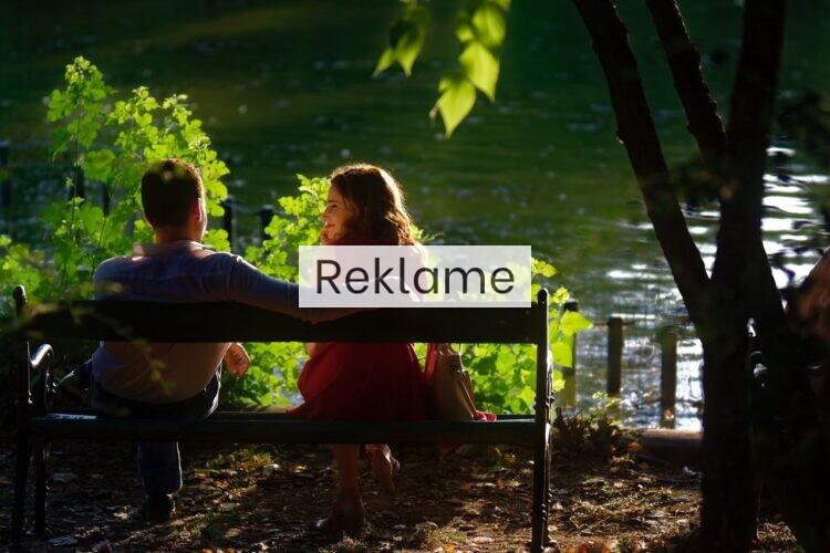 Et par sidder på en bænk i naturen